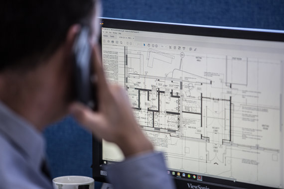 Man sat at computer looking at technical drawing