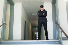 Security guard with sunglasses standing at top of stairs with