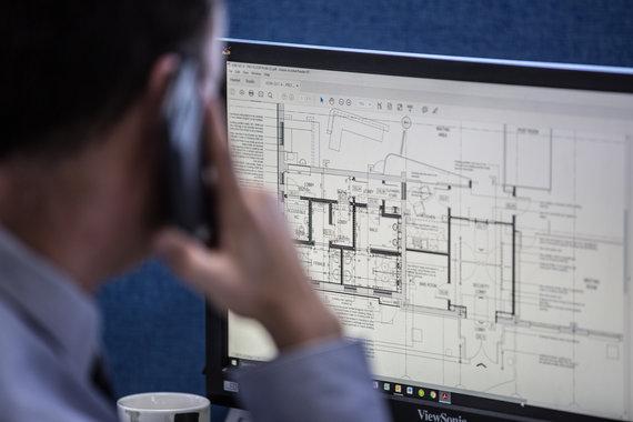 Man sat at computer looking at technical drawing