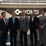 IDL's Far East partner Yonei's team lined up n front of company logo signage and Fastlane logo with demo turnstiles