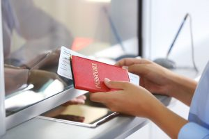 Person stands at passport control with passport in hands