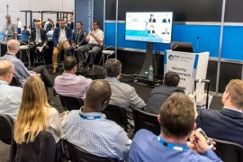 IFSEC panel discussion with man on microphone, three speakers and seated audience