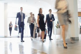 Blurred image of business people moving through office space