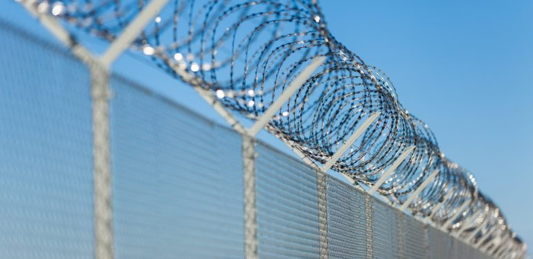 Perimeter fence with coils of barbed wire