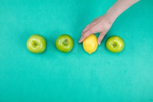 Row of apples with lemon inserted and hand holding lemon