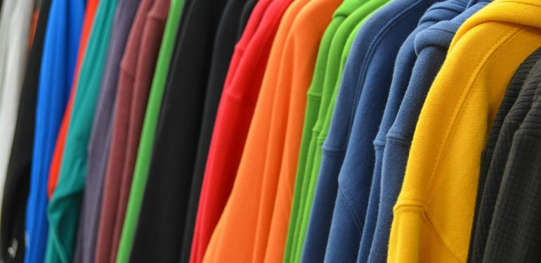 coloured jumpers hanging on a rail